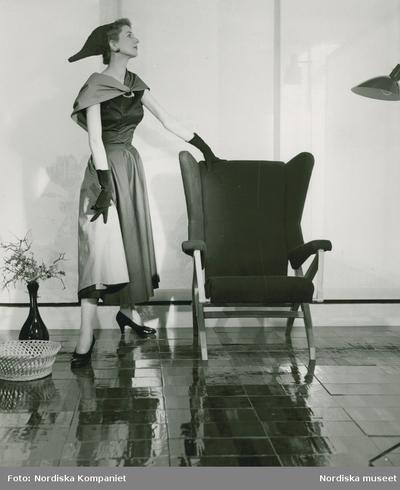 Modell i klänning med sjal och hatt, handskar och pumps, vid en fåtölj.