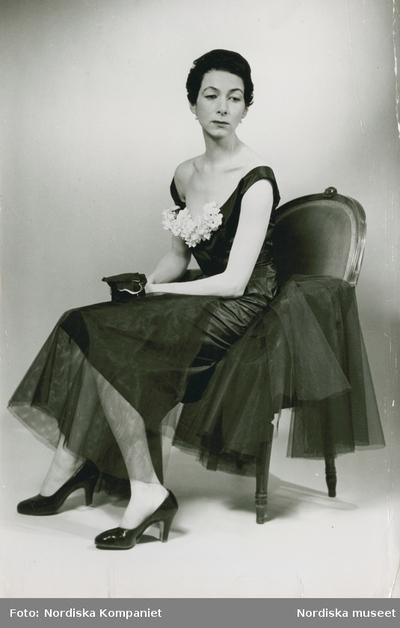 Modell i mörk klänning med blomstergarnityr, handskar och pumps, i en stol.