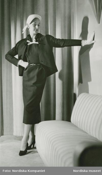 Modell i dräkt med rosett, hatt, handskar och pumps av Christian Dior. Soffa och draperi.