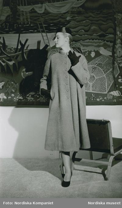 Modell i kappa, hatt, handskar och pumps. Fåtölj och textilkonstverk. Balenciaga.