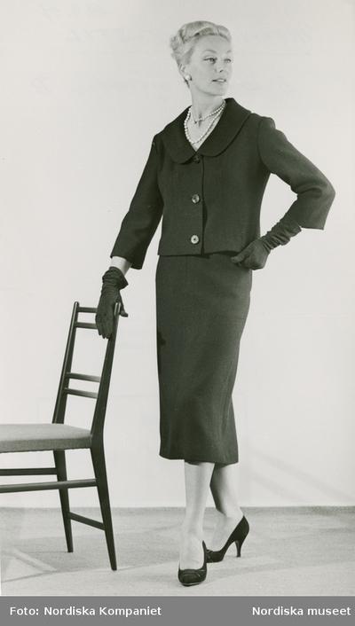 Mönster NK-Stil. Modell i dräkt, handskar, pärlhalsband, örhängen och pumps, vid en stol. Dräkten - Mönster B.