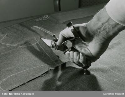 En hand med en tillskärarsax klipper i ett mönsteruppritat tyg. Nordiska Kompaniet.
