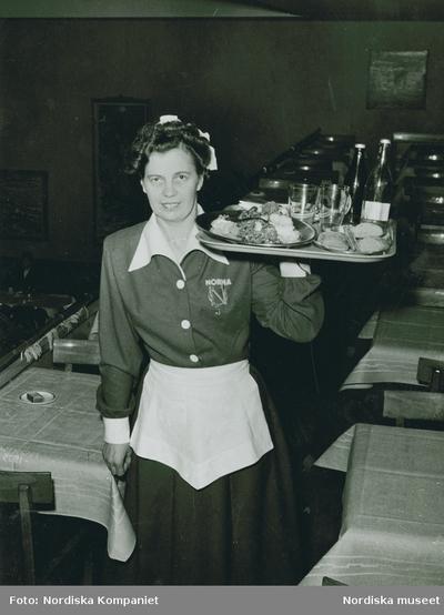 Kvinna i servitrisdräkt med emblem NORMA lyfter en fullastad bricka med ena armen. Text med blyerts på baksidan: