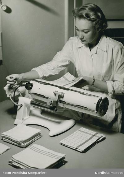 En kvinna manglar handdukar med hjälp av en strykmangel. Påskrift med blyerts på baksidan: