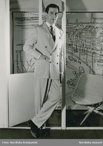 Man i ljus kostym, vit skjorta och slips. I bakgrunden en tecknad stadsmiljö. Bredvid honom en stol i rotting.