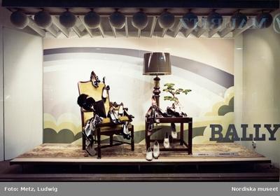 Skyltfönster på Nordiska Kompaniet. Skyltning av Bally-skor. Regnbågsbild, rekvisita - stol, bord, lampa och accessoarer.