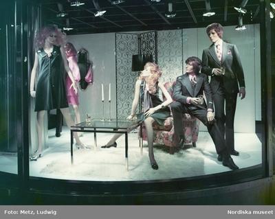Skyltfönster på Nordiska Kompaniet. Skyltdockor i festkläder i grått och rosa. Kostymer och klänningar.