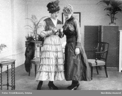 Två kvinnor i Wennbergs allrum, klädda i långklänningar och klackskor. Hatt med pösig kulle. Stolar, växter och en pälsboa i bakgrunden.