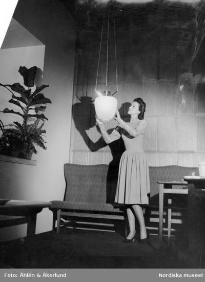 Modell i sandfärgad klänning, ärmar med pärlbroderi. NK:s egen ateljé. Modellen håller i en lampa, soffa och växt i bakgrunden.