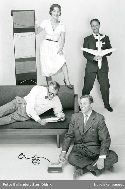 Två män i kostym, en man i vit skjorta och fluga liggande på en soffa, kvinna i vit klänning håller upp textil.