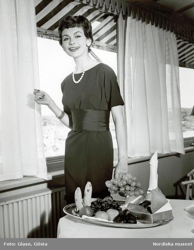 Kvinna i klänning med brett skärp och halsband, framför fönster. Fruktfat på bordet.