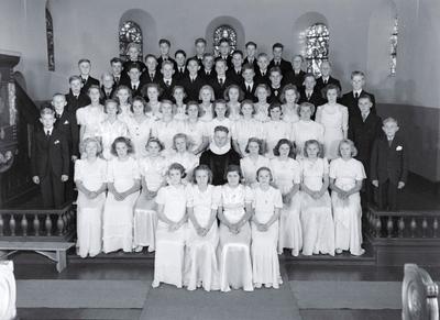 Gruppebilde av konfirmanter og prest i Kråkerøy kirke