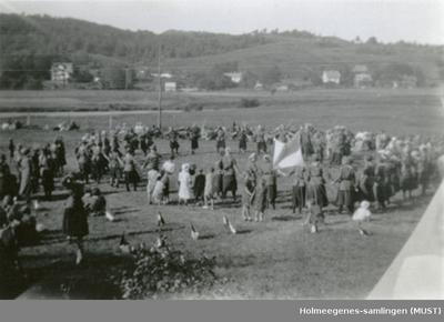 En flokk med speidere står i en stor ring ute på et jorde