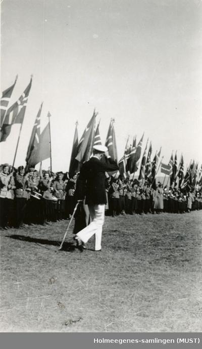 Kong Haakon VII og dronning Maud foran speidere med store norske flagg på speiderleir i 1935