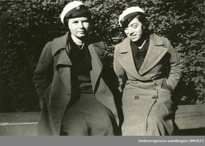 To unge kvinner med russeluer sitter utendørs