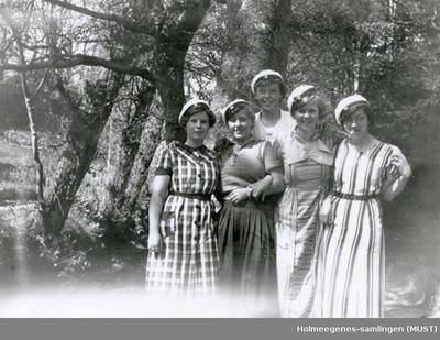 Fem unge kvinner med russeluer utendørs
