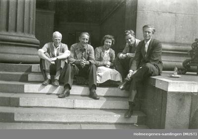 En kvinne og fire menn sittende på en trapp