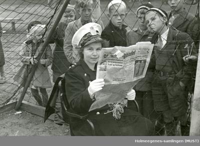 Politikvinne sitter og leser Dagbladet i et fotballmål! En flokk unger ser på gjennom nettet