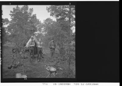 Tre speidere utenfor et telt