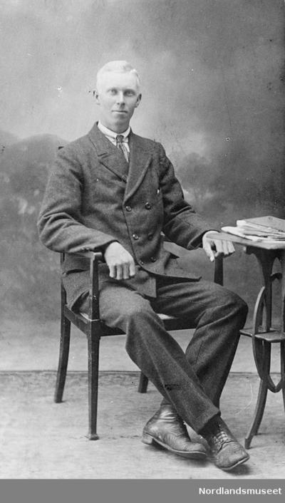 Mann i jakke og bukse som sitter i en stol