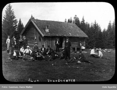 En gruppe menn og ungdommer poserer for fotografen på vollen foran stølshuset på Vensåsseter i Bærumsmarka