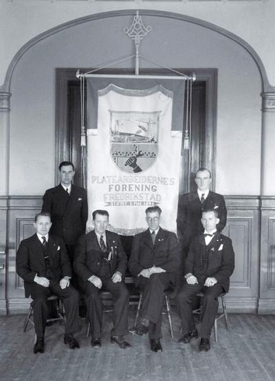 Gruppe på 6 menn med Platearbeidernes Forening sin nye fane