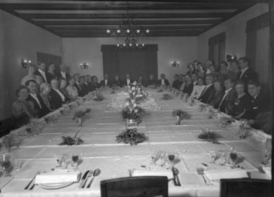 Gruppebilde av sølvbryllupspar med gjester ved dekket langbord
