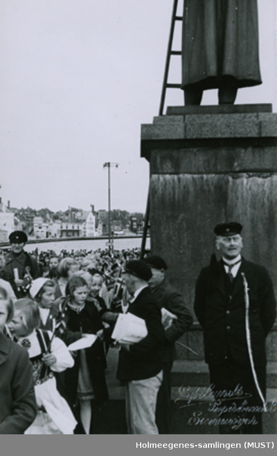Festkledte mennesker ved sokkelen av en statue