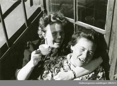 To kvinner ler godt sammen