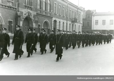 Politifolk marsjerer på rekke og rad (foran politistasjon?)