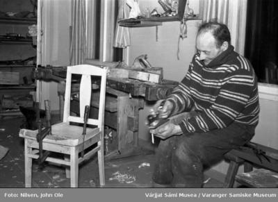 En mann sitter inne i et verksted og høvler på noe