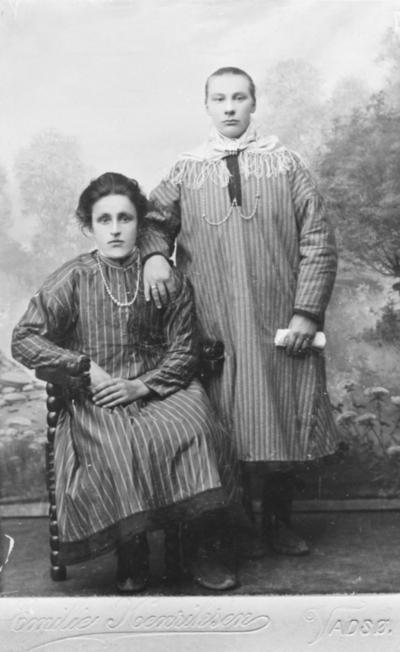 Portrettbilde av to unge kvinner kledd i samekofter