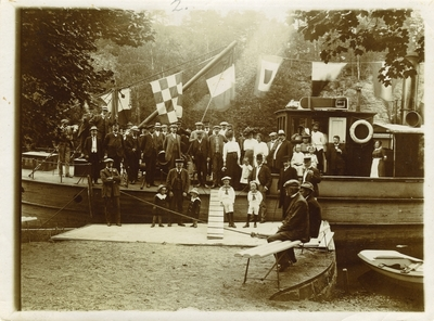 Gruppe med voksne og barn poserer ombord og ved ukjent båt med signalflagg