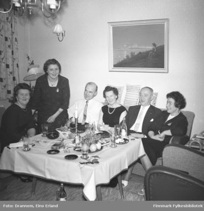 Pentkledte mennesker samlet i stua til familien Drannem i Hammerfest