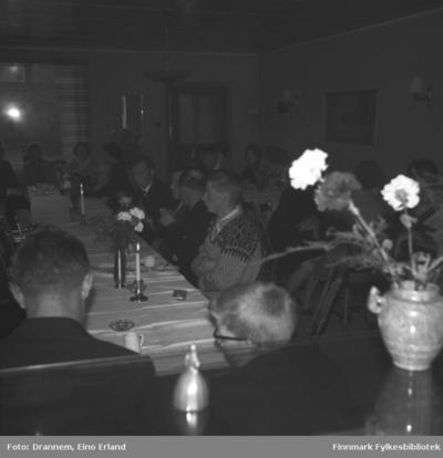 Mange personer sitter ved langbord i et lokale i Neiden