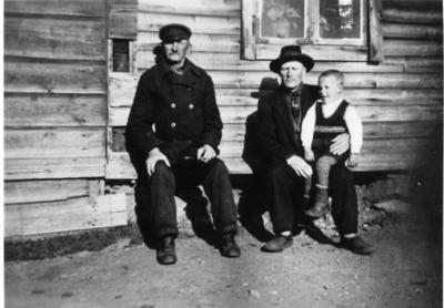 De sitter i solveggen på gårdsplassen til Tuomainengården i Vadsø og året er ca