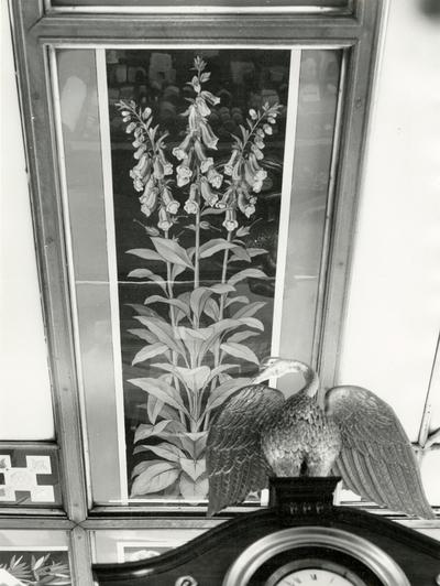 Fotografi av interiørdetalj med glassmaleri av revebjelle samt svanefigur
