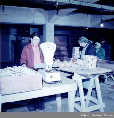 Foto av kvinner i gang med å pakke og veie klippfisk på ei brygge