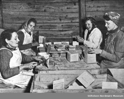 Fire kvinner som sitter rundt et bord og pakker klippfisk i esker