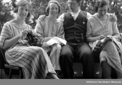 Tre kvinner og en mann sitter utendørs