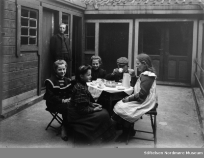 Fire jenter og to gutter har teselskap utendørs