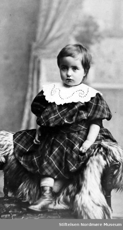 Portrett av en liten pike iført kjole og blondekrage