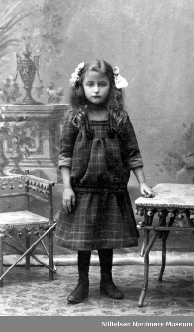 Portrett av en ung pike iført kjole og hårsløyfer