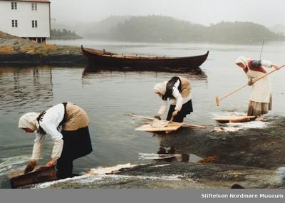 serie - Arrangert bilde hvor vi ser tre jenter som vasker klippfisk på tradisjonell måte iført tidsriktige klær