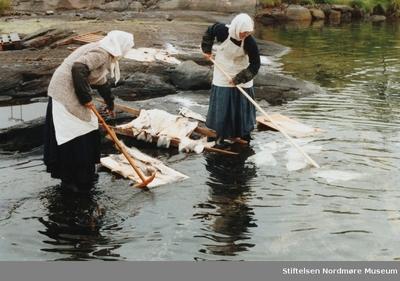 serie: Arrangert bilde hvor vi ser to jenter som vasker klippfisk på tradisjonell måte iført tidsriktige klær