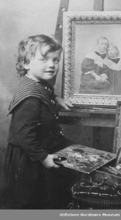 Ernst Ranheimsæter med malersett og et fotografi av to piker på et staffeli