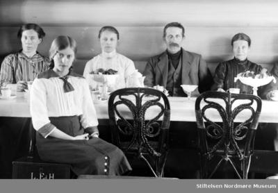 Familie samlet rundt bord for fotografering