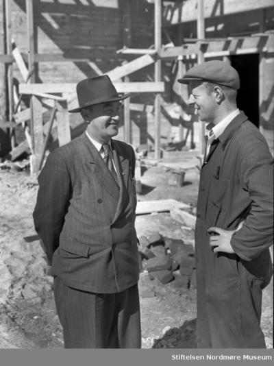 To personer i samtale foran rådhuset som er under oppføring (gjenreising etter 1940)