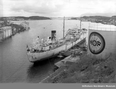 Informant Anne Lise Tømmervåg: Texaco`s tankskip NUEVA ANDALUCIA ligger ved kaia til det som en gang var Bjørnehaugen verft for tanking av drivstoff til NOR-tanken - ved Bjørnehaugen på Nordlandet