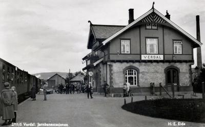 Verdal stasjon med nordgående tog og reisende på plattformen